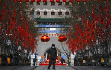 A security guard wearing a face mask walks through a quiet main Qianmen Street, a popular tourist spot, in Beijing, Sunday, Feb. 16, 2020.