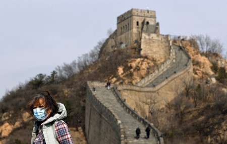 A woman wearing a protective face mask visits the Badaling Great Wall of China after it reopened for business following the new coronavirus outbreak in Beijing, China, Tuesday, March 24, 2020.
