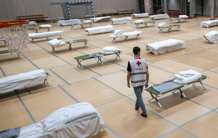 A Red Cross volunteer looks at beds set up for homeless people in the gymnasium of Uranienborg school, which is closed due to the corona eruption, in Oslo, Thursday, March 26, 2020.