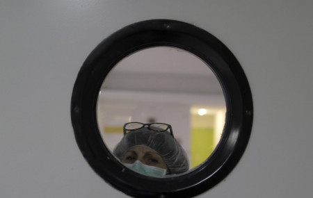 A health worker wearing a face mask to protect from coronavirus, looks out of from a window at a nursing home in Madrid, Spain, Tuesday, March 31, 2020.