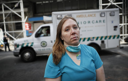 Registered Nurse Elizabeth Schafer, 36, of South St. Paul, Minn., stands for a portrait before entering Beth Israel Mount Sinai Hospital for her second day volunteering to combat the COVID-19 pandemic, Wednesday, April 1, 2020, in New York.