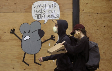- In this May 2, 2020, file photo, a man and woman wearing masks to prevent the spread of the coronavirus walk past a cartoon advising people to wash their hands on a boarded up storefront in San Francisco.