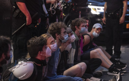 Protesters who were arrested by police for breaking a curfew during a solidarity rally calling for justice over the death of George Floyd, sit on a sidewalk as they wait to be taken away in a van on Thursday, June 4, 2020, in New York.