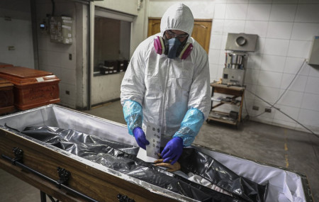 An employee takes the fingerprints of a woman who died from the new coronavirus before her remains are cremated at La Recoleta crematorium in Santiago, Chile, Saturday, June 27, 2020.