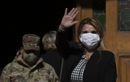 Bolivia's interim President Jeanine Anez, wearing a face mask to help curb the spread of the new coronavirus, waves during a procession Corpus Christi, in La Paz, Bolivia, Thursday, June 11, 2020.