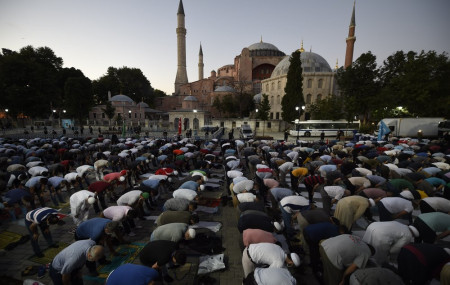 Muslims offer their evening prayers outside the Byzantine-era Hagia Sophia, one of Istanbul's main tourist attractions in the historic Sultanahmet district of Istanbul, following Turkey's Council of State's decision, Friday, July 10, 2020.