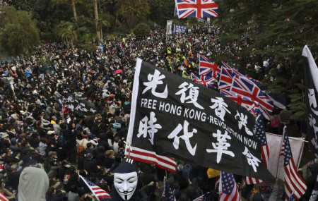 In this Sunday, Jan. 19, 2020 file photo, participants wave British and U.S. flags during a rally demanding electoral democracy and call for boycott of the Chinese Communist Party and all businesses seen to support it in Hong Kong.