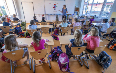 Teacher Francie Keller welcomes the pupils of class 3c in her classroom in the Lankow primary school to the first school day after the summer holidays in Schwerin, Germany, Monday, Aug. 3, 2020.