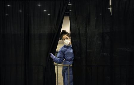 Diana Vega, a registered respiratory therapist, peeks through a curtain during setup at a temporary coronavirus testing site Monday, Aug. 3, 2020, in Las Vegas.