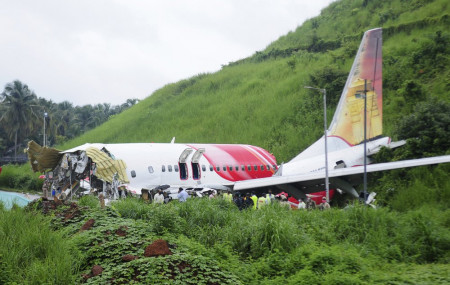 Officials stand on the debris of the Air India Express flight that skidded off a runway while landing in Kozhikode, Kerala state, India, Saturday, Aug. 8, 2020.