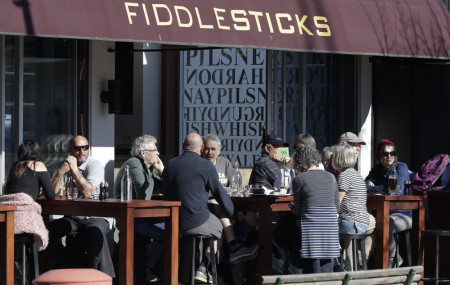 Customers at a cafe enjoy lunch in the sunshine in Christchurch, New Zealand, Sunday, Aug. 9, 2020. New Zealand marked a 100 days of being free from the coronavirus in its communities Sunday.