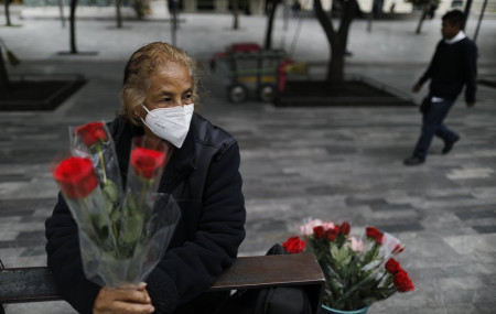 Wearing a mask to curb the spread of the new coronavirus, Martha Gonzalez Reyes, 76, sells roses outside Metro Hidalgo in central Mexico City, Monday, Aug. 10, 2020.