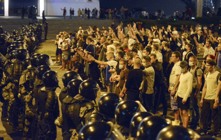In this file photo taken on Sunday, Aug. 9, 2020, people argue with police during a rally after the Belarusian presidential election in Minsk, Belarus.