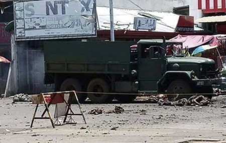 In this photo provided by the Philippine Red Cross, a military truck lies at an area where a bomb exploded at the town of Jolo, Sulu province, southern Philippines, Monday, Aug. 24, 2020.