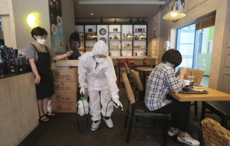 A worker disinfects as a precaution against the coronavirus at a cafe in Goyang, South Korea, Tuesday, Aug. 25, 2020.