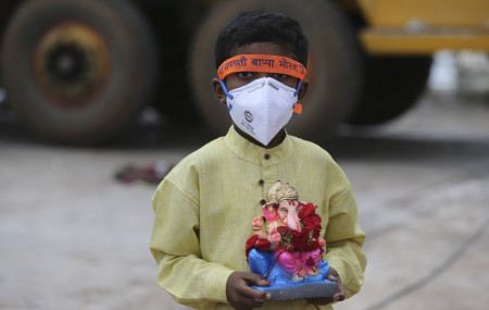 An Indian child wearing a mask as a precaution against the coronavirus carries an idol of elephant-headed Hindu god Ganesha to immerse in Saroornagar Lake on the final day of Ganesh Chaturthi festival in Hyderabad, India, Tuesday.