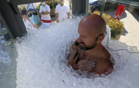 Austrian ice swimmer Josef Koeberl is standing in a glass cabin filled with ice try to break the world record for a human to stay side an ice box in Melk, Saturday, Sept. 5, 2020.