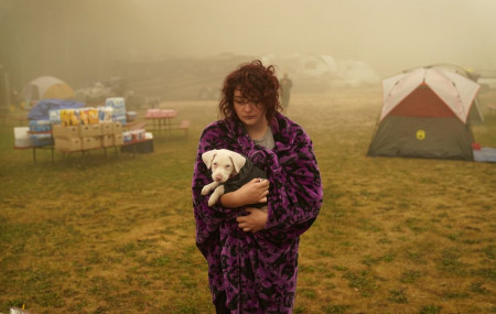 Shayanne Summers holds her dog Toph while wrapped in a blanket after several days of staying in a tent at an evacuation center at the Milwaukie-Portland Elks Lodge, Sunday, Sept. 13, 2020, in Oak Grove, Oregon.
