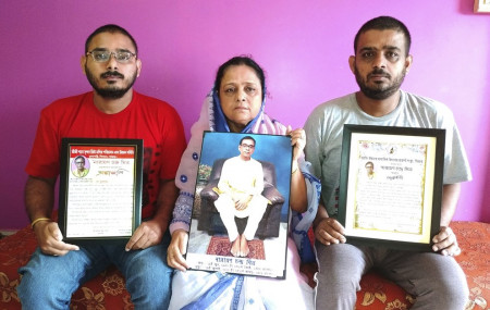 Anindita Mitra, 61, flanked by her sons Satyajit Mitra, right and Abhijit Mitra, pose with portraits of her husband late Narayan Mitra, at her house in Silchar, India, Sunday, Sept. 13, 2020.