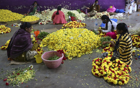 Flower vendors, some wearing face masks as a precaution against coronavirus, prepare garlands at a wholesale market in Bengaluru, India, Thursday, Sept. 24, 2020.