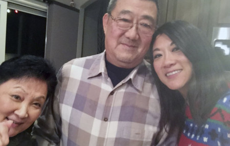 This December 2016 photo provided by the family shows, from left, Lu Wang, Ming Wang and Anne Peterson. Ming Wang, 71, was sickened in March 2020 on a cruise from Australia with his wife.