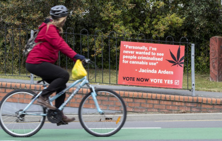 A cyclist rides past a sign in support of making marijuana legal in Christchurch, New Zealand, Thursday, Oct. 15, 2020.