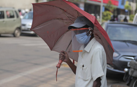 A man wearing a face shield as a precautionary measure against the coronavirus walks on a street in Hyderabad, India, Tuesday, Oct. 27, 2020.