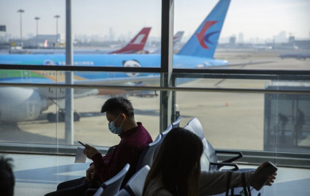 Travelers wearing face masks to protect against the coronavirus sit at a boarding gate at the Shanghai Hongqiao International Airport in Shanghai, Friday, Nov. 6, 2020.