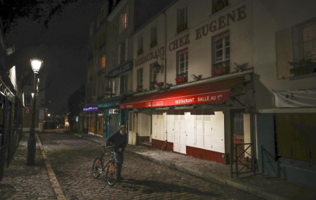 In this Dec. 15, 2020 file photo, a man pushes his bicycle along a row of closed restaurants in Montmartre, during the new imposed curfew in Paris.