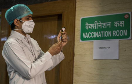 In this Jan. 8, 2021, file photo, a health worker performs a trial run of COVID-19 vaccine delivery system in New Delhi, India. The global death toll from COVID-19 has topped 2 million.