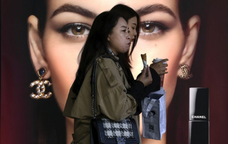 In this Oct. 19, 2020, file photo, women eating snack walk by a Chanel cosmetic shop at the capital city's popular shopping mall in Beijing.