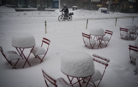 A man delivers food on his electric bicycle as he rides past snow-covered dining tables in midtown during a snowstorm, Monday, Feb. 1, 2021, in New York.