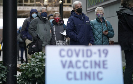 In this an. 24, 2021, file photo, people stand near a sign as they wait in line to receive the first of two doses of the Pfizer vaccine for COVID-19 at a one-day vaccination clinic set up in an Amazon.com facility in Seattle.