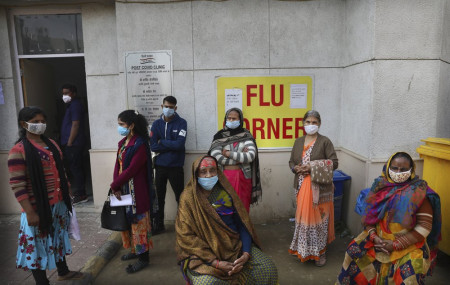 People wait outside a health center to get tested for COVID-19 in New Delhi, India, Thursday, Feb. 11, 2021.