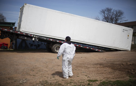 In this April 7, 2020 file photo, gravedigger Thomas Cortez watches as a refrigerated trailer is delivered to keep pace with a surge of bodies arriving for burials at the Hebrew Free Burial Association's cemetery in the Staten Island borough of New York.