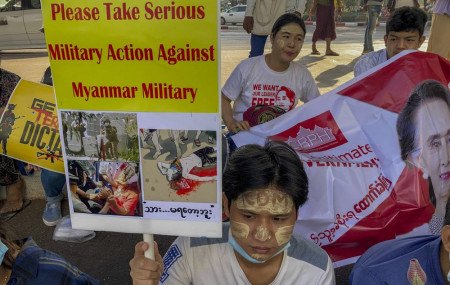An anti-coup protester holds a placard requesting military action against Myanmar military in Yangon, Myanmar Thursday, Feb. 25, 2021.