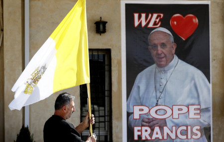 A Christian priest holds a Vatican flag as he walks by a poster of Pope Francis during preparations for the Pope's visit in Mar Youssif Church in Baghdad, Iraq, Friday, Feb. 26, 2021.