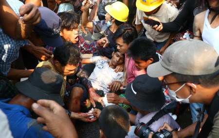 Anti-coup protesters surround an injured man in Hlaing Thar Yartownship in Yangon, Myanmar Sunday, March 14, 2021.