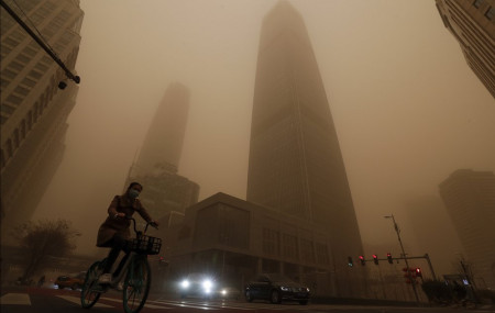 A cyclist and motorists move past office buildings amid a sandstorm during the morning rush hour in the central business district in Beijing, Monday, March 15, 2021.