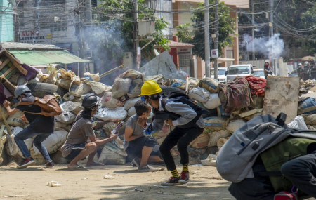 Armed riot policemen charge after firing teargas a rubber bullets as anti-coup protesters abandon their makeshift barricades and run in Yangon, Myanmar Tuesday, March 16, 2021.