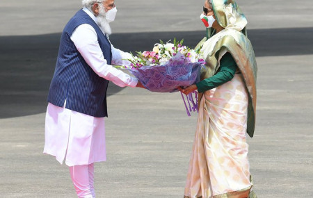 n this photo provided by Prime Minister of India Narendra Modi's twitter handle, Indian Prime Minister Narendra Modi receives a bouquet of flowers from Bangladesh's Prime Minister Sheikh Hasina in Dhaka, Bangladesh, Friday, March 26, 2021.