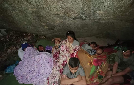 In this photo provided by Free Burma Rangers, villagers shelter in the open due to airstrikes, Saturday, March 27, 2021, in Deh Bu Noh, in Karen state, Myanmar.