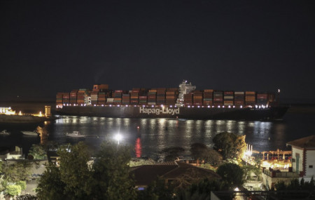 A cargo ship sails through the town of Suez, Egypt, Tuesday, March 30, 2021 as traffic resumed through the Suez canal after it was blocked by a massive ship that had been stuck sideways for nearly a week.