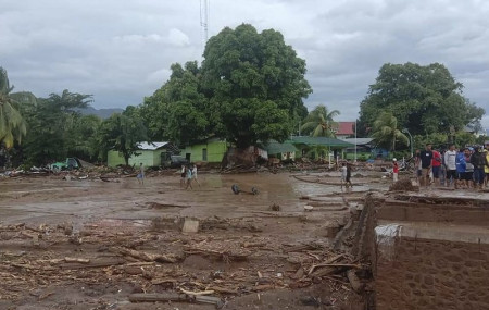 Residents inspect the damage at a village hit by flash flood in East Flores, Indonesia, Sunday, April 4, 2021.