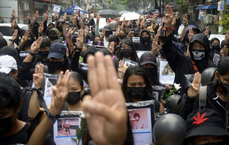 Anti-coup protesters flash three-fingered symbol of resistance as they gather to pray for those who died during a protest against the military in Yangon, Myanmar, Monday, April 5, 2021.