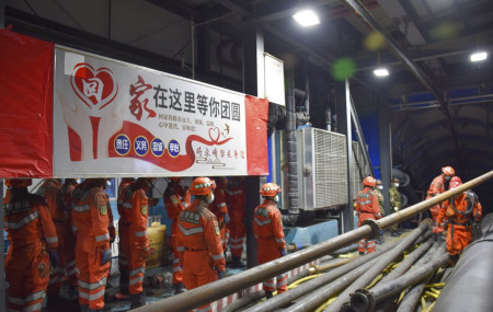 In this photo released by Xinhua News Agency, rescue workers stand near a banner which reads: