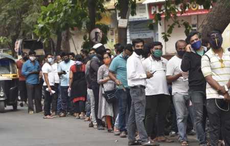 People wait in queues outside the office of the Chemists Association to demand necessary supply of the anti-viral drug Remdesivir, in Pune, India, Thursday, April 8, 2021.