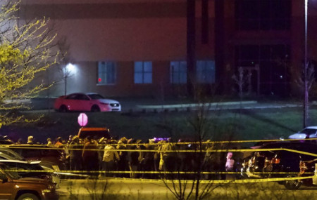 People stand outside a FedEx facility near Indianapolis International Airport after a shooting with multiple victims was reported late Thursday night, April 15, 2021.