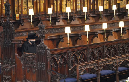 Britain's Queen Elizabeth II sits alone in St. George's Chapel during the funeral of Prince Philip, the man who had been by her side for 73 years, at Windsor Castle, Windsor, England, Saturday April 17, 2021.