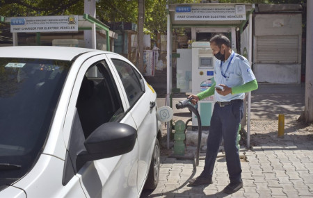 A driver of an electric car charges his vehicle at public charging station in New Delhi, India, Thursday, April 1, 2021.